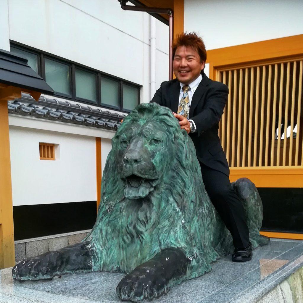 三越ライオン像 にまたがる榊原平。三井越後屋発祥の地松阪にて
