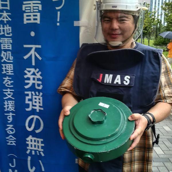 今「地雷」を抱えてます。防護服とヘルメットとフェイスカバーつけてます。 グローバルフェスタ グロフェスー 場所: シンボルプロムナード公園 地雷(模型)を抱えた榊原平