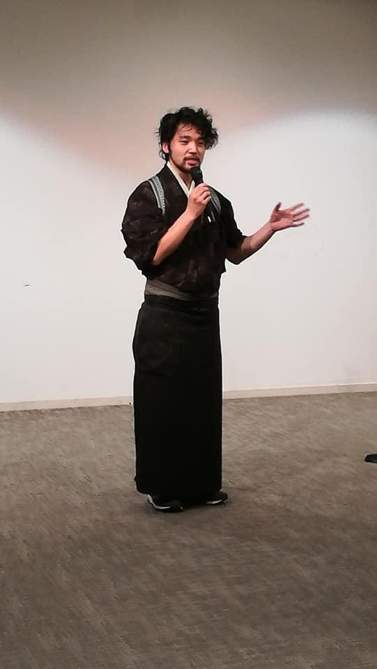 黒い着物を着た男性が立っています。世界食料デ-記念シンポジウム