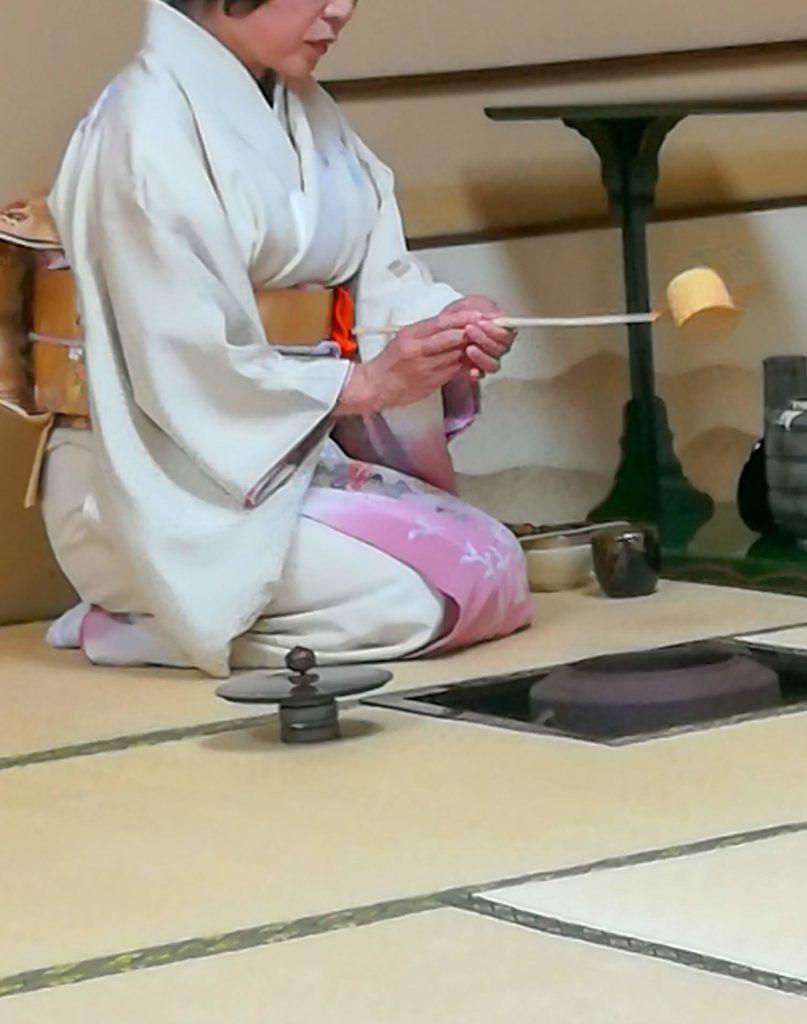 着物を着た女性が正座してお茶をしています。