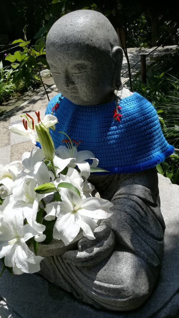 白い百合の花を抱えた花想い地蔵。