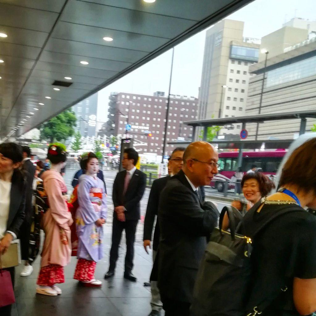 舞子さんや男性たちが新幹線のホームでエマニュエル・マクロン大統領を乗せた新幹線をお迎えしています。