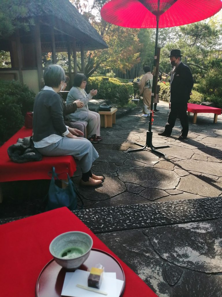 男女が野点のお茶とお菓子を楽しんでいます