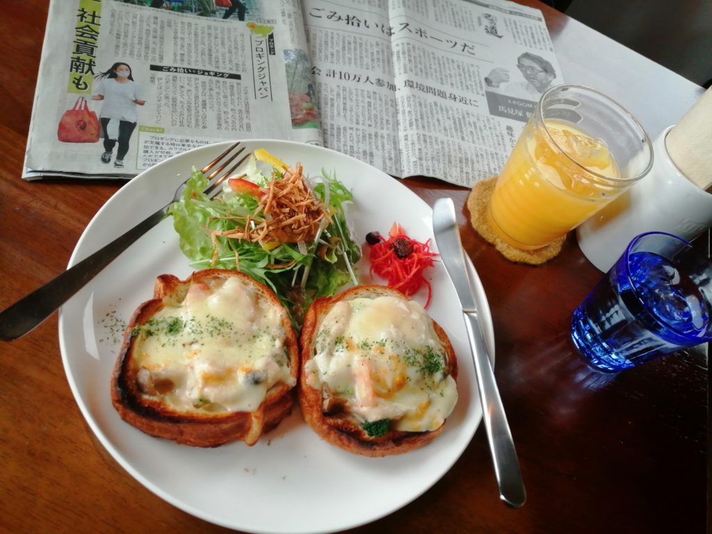 A plate with food, a glass of orange juice, and a blue glass of water 食事ののった皿とオレンジジュースのグラス、そして水の入った青色のグラス