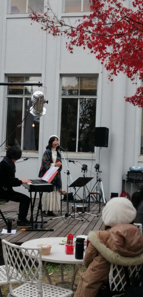 歌を歌う女性高野陽子さんとそれを聞く人々 マルシェ・ド・ノエル