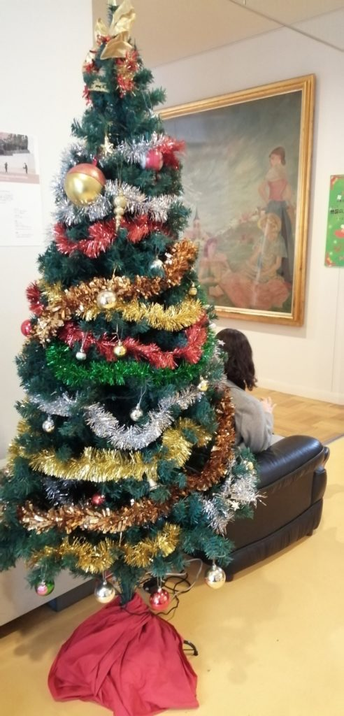 "There is a picture of Tsuguharu Fujita ""Spring in Normandy"" and a Christmas tree decorated in front of it. .. 藤田嗣治の絵画「ノルマンディーほ春」の前に飾られたクリスマス・ツリーが置かれている。 マルシェ・ド・ノエル"